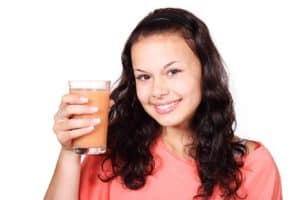 Woman holding up a glass of juice and smiling
