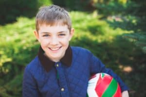 Child wearing a blue jacket, smiling, and holding a soccer ball