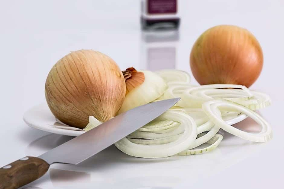 Yellow onions sliced up on a plate with a cutting knife sitting beside