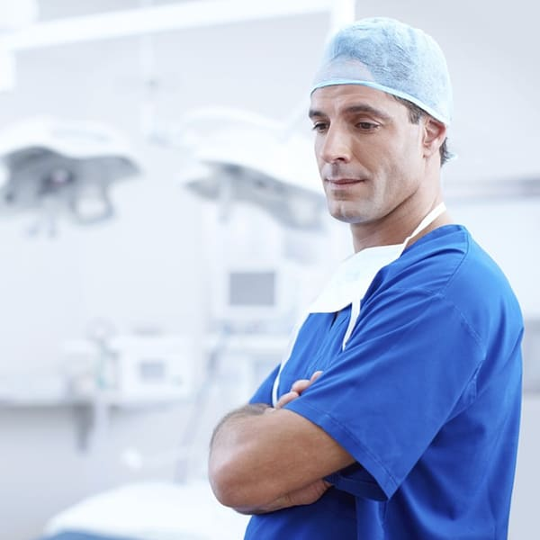Surgeon in blue scrubs standing in a medical office staring off to the side with his arms crossed.