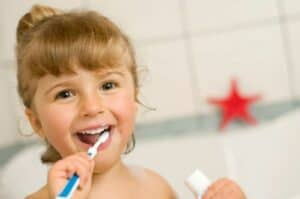 Cute little girl smiling, brushing her teeth in the bathroom